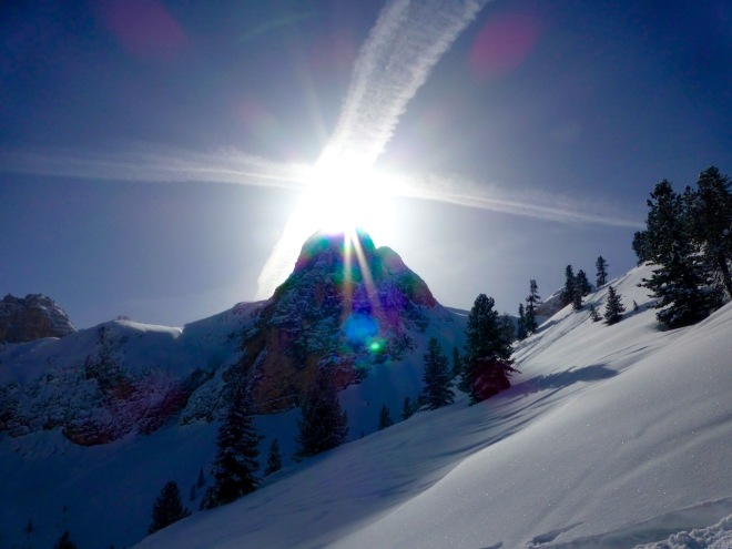 Sun flashes above Mountain Peaks