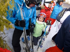 father and smiling small daughter in ski lift line